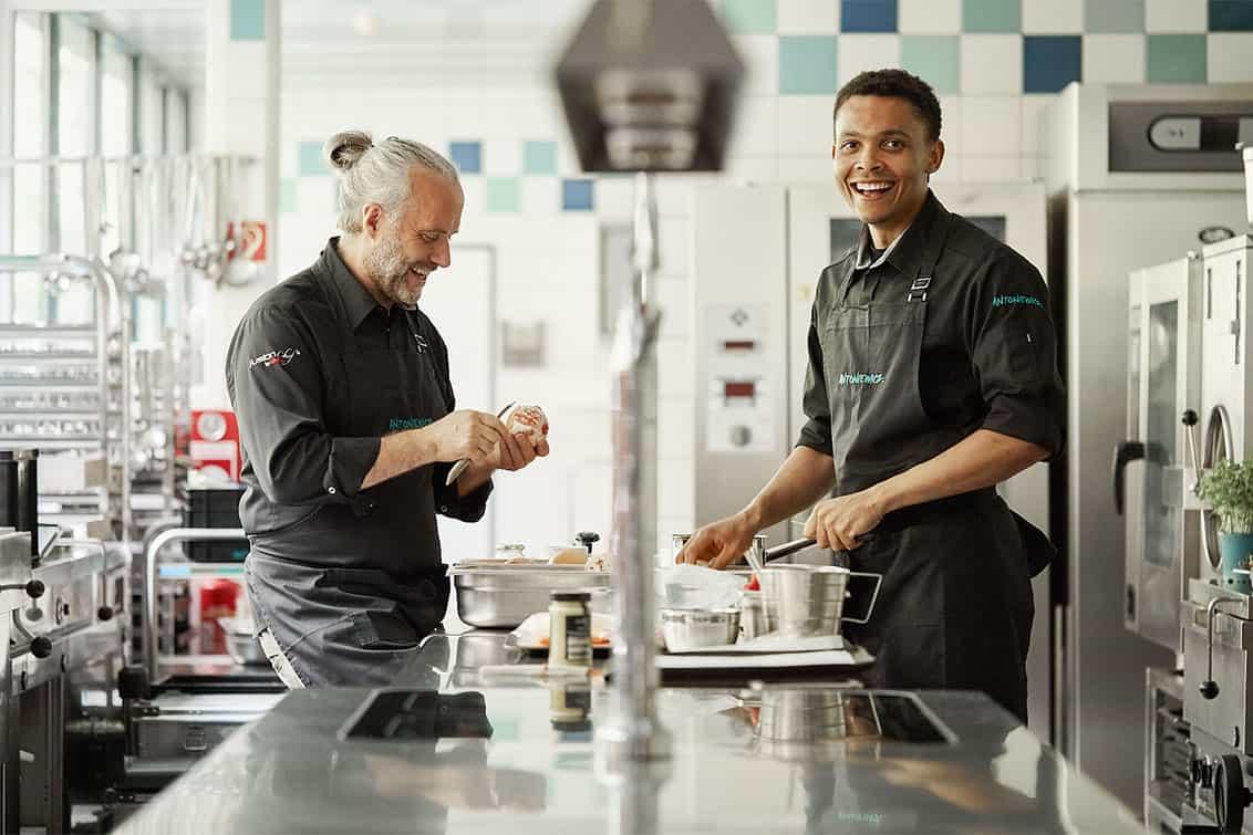 Heiko Antoniewicz in der Küche beim Zubereiten mit weiterer Person